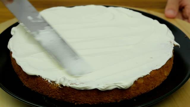 chef's spreading cream on cake slow motion