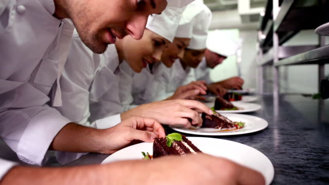 Chefs standing in a row garnishing dessert plates