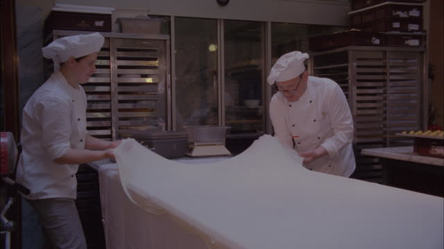 Chefs stretch pastry dough over a table.