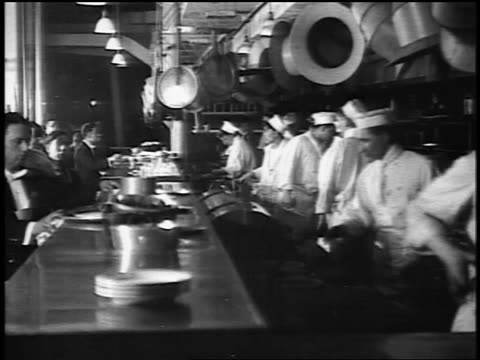 b/w 1916 chefs working in galley kitchen of restaurant / jump cuts / newsreel - newsreel stock videos and b-roll footage