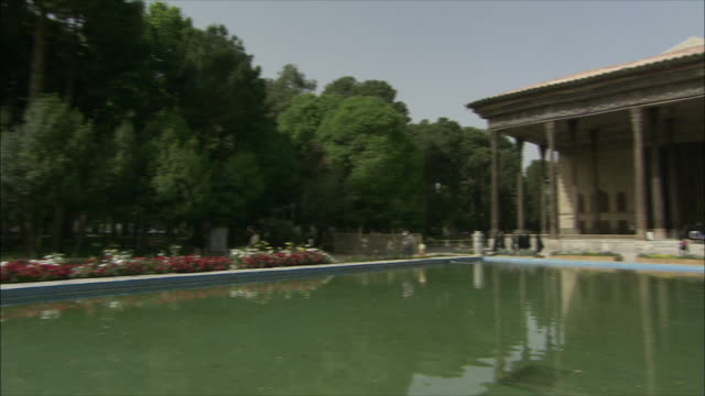 WS PAN Chehel Sotoun pavilion with pool and flowers in foreground, Isfahan, Iran