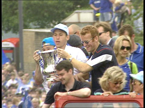 Chelsea FA Cup victory parade ITN Chelsea MS Chelsea players atop opentop bus as one holds FA Cup and shows it to crowds TLMS Bus along thru crowds...