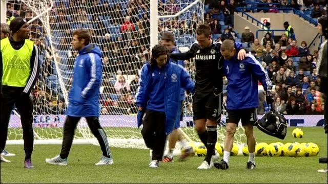 london stamford bridge ext john terry receiving treatment for injury on pitch terry hobbling as helped off pitch - スタンフォードブリッジ点の映像素材/bロール