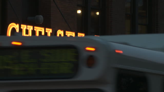 Chelsea Market Neon sign.  A bus drives through and the sign ripples in the heat