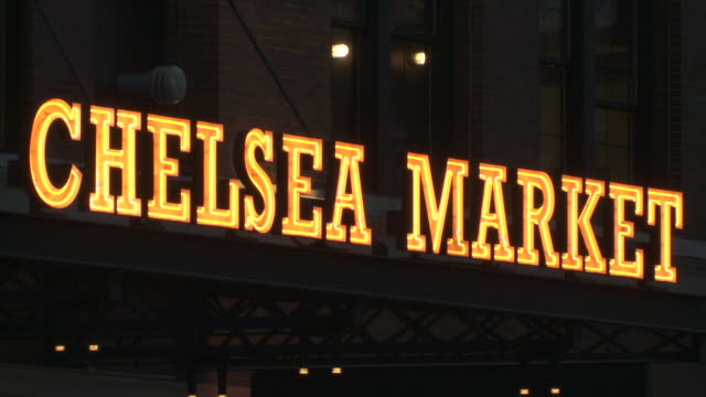 chelsea market neon sign.  a bus drives through and the sign ripples in the heat - chelsea new york stock videos & royalty-free footage