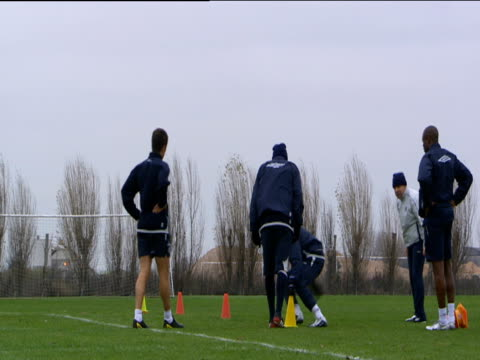 Chelsea players run short sprints to cones during Chelsea FC training session