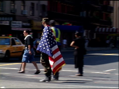 vídeos de stock, filmes e b-roll de chelsea september 2001 african american man wearing fatigues large american flag draped over shoulders crosses street at 7th avenue 23rd street - 2001