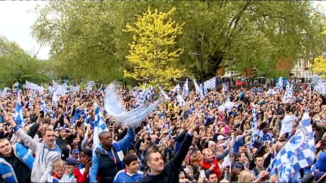 victory parade through streets High Angle shot of mass Chelsea fans celebrating Didier Drogba amongst other Chelsea players with trophy held behind