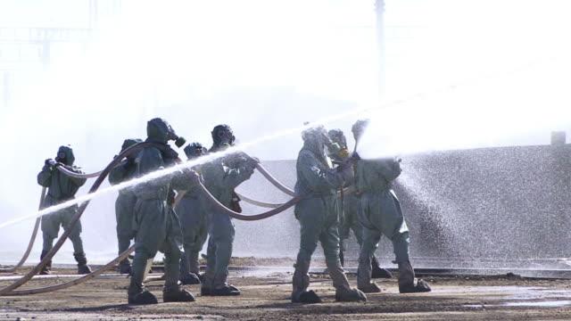 vídeos y material grabado en eventos de stock de equipo de química en máscara de gas agua que fluye - parque de bomberos