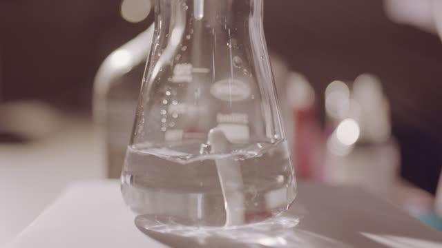 chemische reaktion im schüttelmittelbecher - becherglas stock-videos und b-roll-filmmaterial