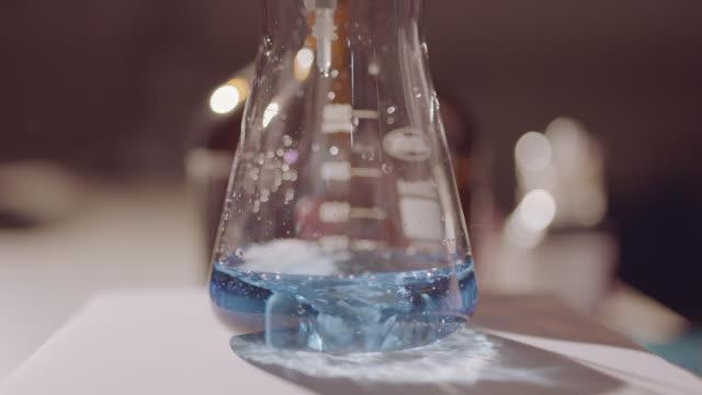 stockvideo's en b-roll-footage met chemische reactie in schudden vloeibaar bekerglas - medisch specimen