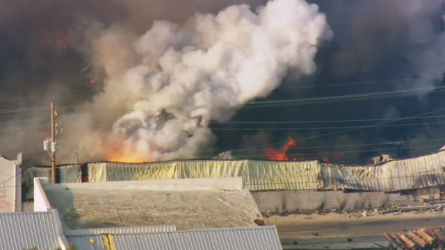 chemical warehouse burning and smoke arising due to fire / united states - warehouse点の映像素材/bロール