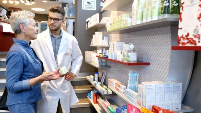 apotheke beraten kunden mit medizin im store - apothekerberuf stock-videos und b-roll-filmmaterial