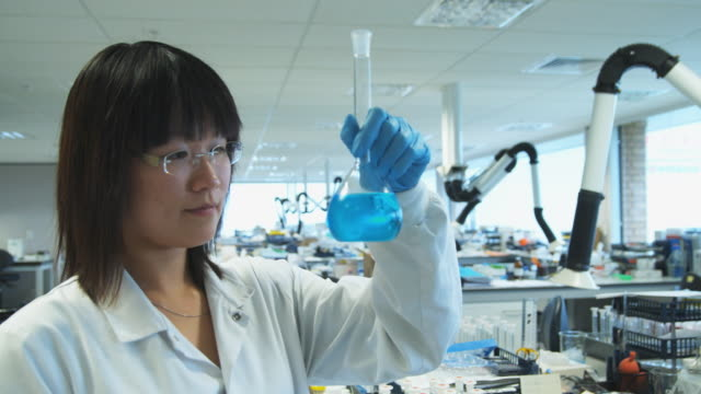 MS Chemist analyzing blue liquid in pharmaceutical laboratory / Auckland, New Zealand
