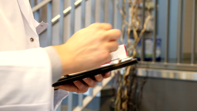 chemist analyzing medicines through digital tablet - prescription medicine stock videos & royalty-free footage
