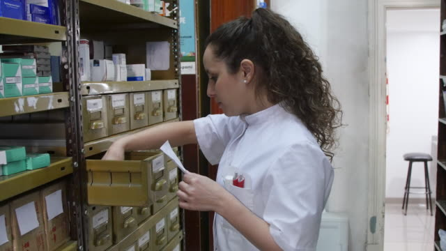 chemist checking medicines in drawers at pharmacy - rack stock videos & royalty-free footage