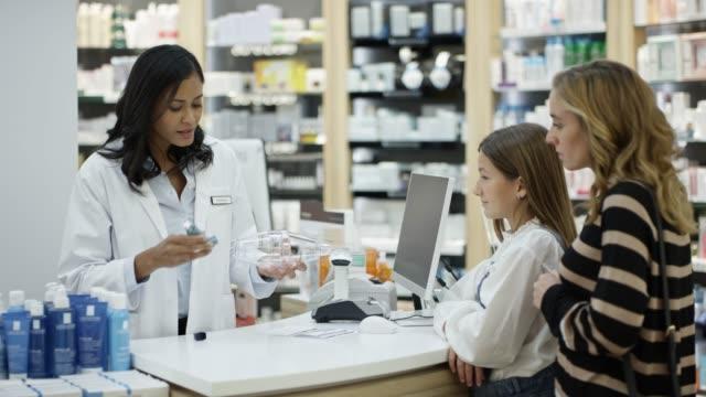 vidéos et rushes de chimiste expliquant l'inhalateur d'asthme à la fille en magasin - inhalateur