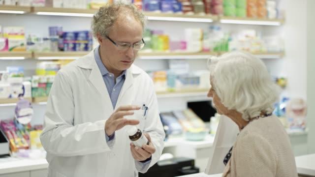 vídeos y material grabado en eventos de stock de químico explicando medicación al cliente senior - emoción positiva