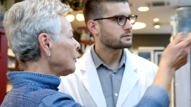 店で顧客に薬を説明する化学者 - 説明する点の映像素材/bロール