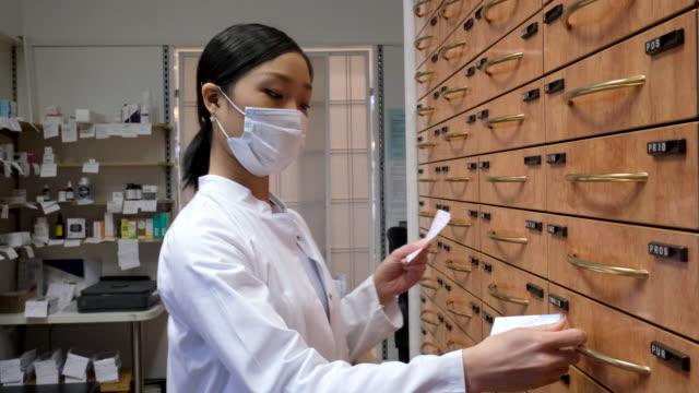 chemiker auf der suche nach verschreibungspflichtigen medikamenten in einem regal - prescription medicine stock-videos und b-roll-filmmaterial
