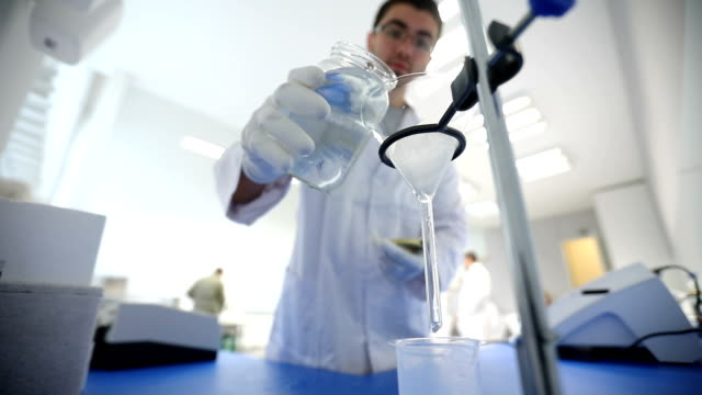 chemist pouring filtering sample through filter paper - separating laboratory stock videos and b-roll footage