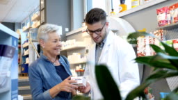 Chemist talking over medicine with smiling woman