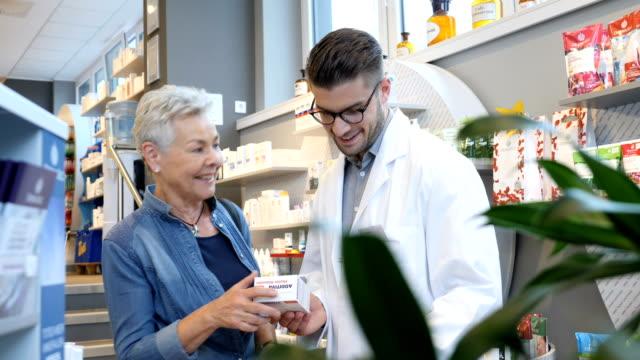 笑顔の女性と話して薬以上の化学者 - 説明する点の映像素材/bロール