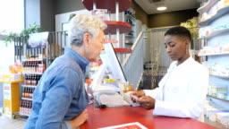 Chemist talking over prescription with customer