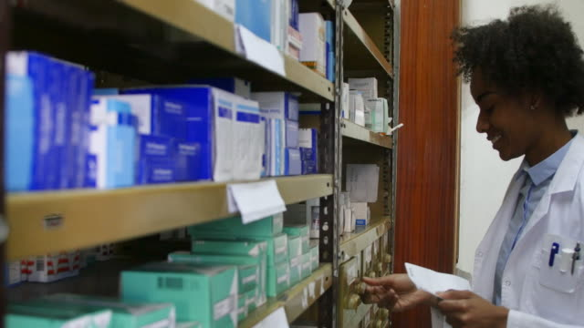 chemist with document picking up medicine on rack - rack stock videos & royalty-free footage
