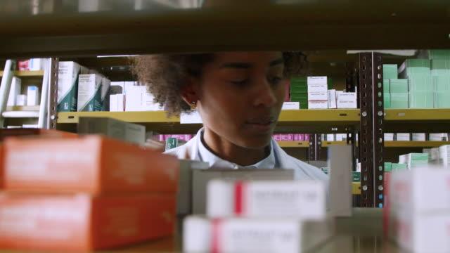 vídeos de stock, filmes e b-roll de químico com tablet pc examinando medicamentos em rack - grupo grande de objetos