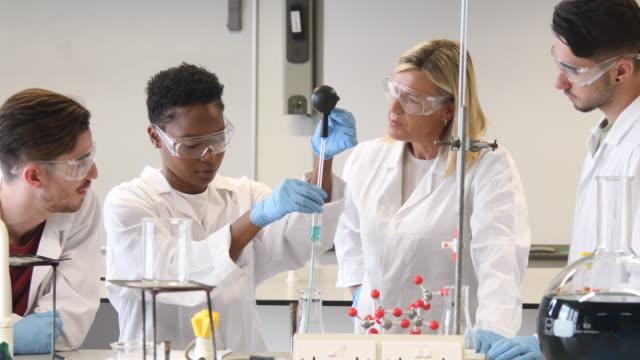 vídeos y material grabado en eventos de stock de clase de química con la maestra explicando a sus alumnos - etnia