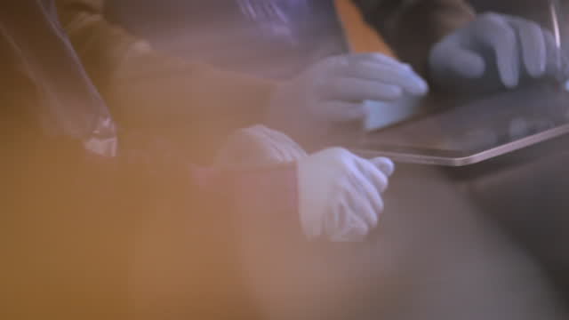 Hands of students using tablets to conduct chemistry lab experiment