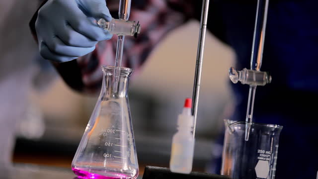 a chemistry students drains liquid into a beaker and the reaction causes it to change color. - chemikalie stock-videos und b-roll-filmmaterial