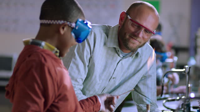 a chemistry teacher and student get excited during a bunsen burner experiment. - bunsen burner stock videos & royalty-free footage