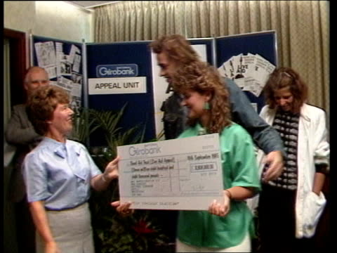 stockvideo's en b-roll-footage met cheque presented to bob geldof itn milk st two female workers from national girobank present large girobank cheque of 11000 pounds to bob geldof and... - bob geldof