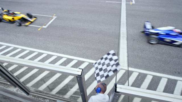 vídeos de stock e filmes b-roll de ld chequered flag being waved to the formula drivers crossing the finish line - competição