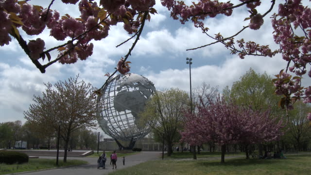 vídeos de stock, filmes e b-roll de cherry blossom trees, flushing meadows park / ny world's fair unisphere - springtime - flushing meadows corona park