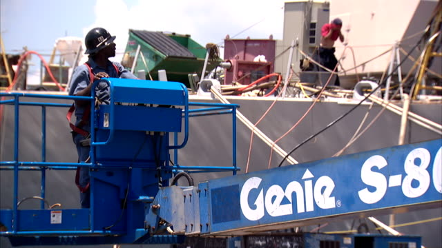 a cherry picker carries a construction worker to the uppermost deck of a ship. - cherry picker stock videos & royalty-free footage