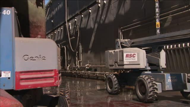 a cherry picker drives alongside a ship. - cherry picker stock videos & royalty-free footage