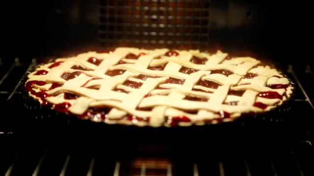 vídeos de stock e filmes b-roll de cherry pie cooking in oven - fazer doces
