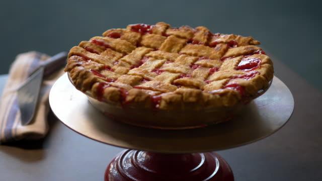 vídeos y material grabado en eventos de stock de cherry pie with lattice crust on pie stand - clase de economia domestica