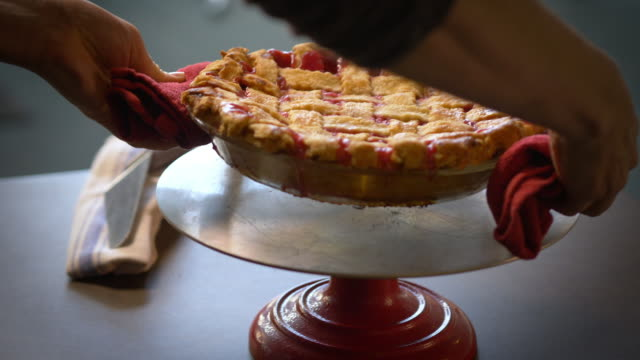 Cherry pie with lattice crust right from the oven being placed on pie stand