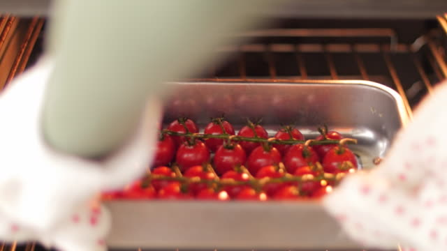cherry tomatoes in the oven - oven mitt stock videos and b-roll footage