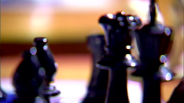 PAN chess pieces on board black queen moves black male fingers steady game piece CU Queen chess piece standing next to king w/ pawn