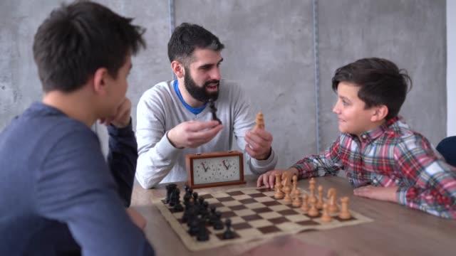チェスの先生がチェスのやり方を教える - 余暇 ゲームナイト点の映像素材/bロール