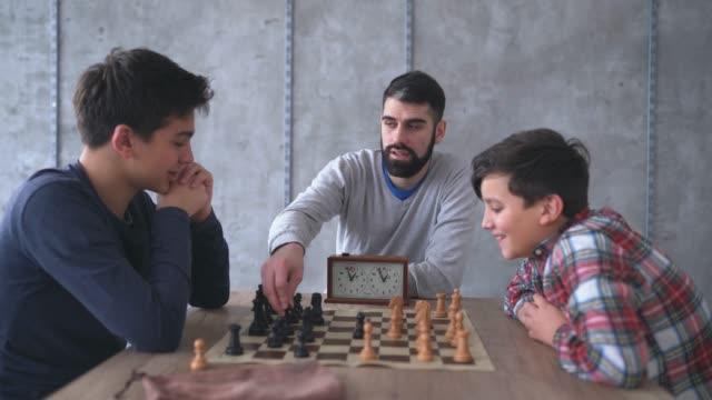 チェスの先生は2人の少年を見てチェスをする - 余暇 ゲームナイト点の映像素材/bロール