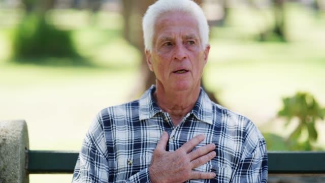 胸の痛みと息切れは、心臓発作の兆候であります - ベンチ点の映像素材/bロール