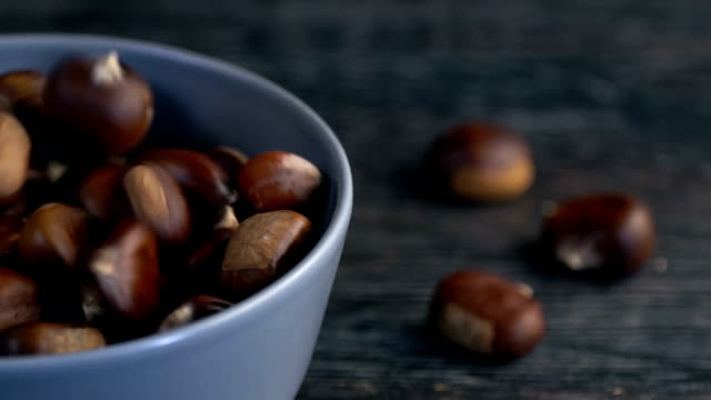 chestnut falls from high into the bowl, slow motion. - nutshell stock videos & royalty-free footage