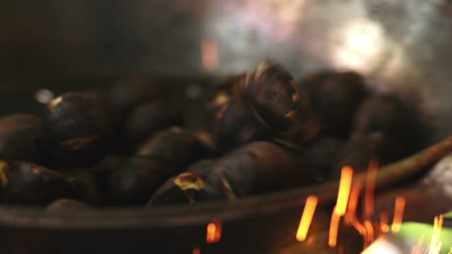 Chestnuts roasting in cast iron skillet over flame, slow motion