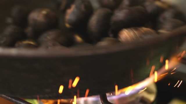 chestnuts roasting in cast iron skillet over flame, slow motion - marrone video stock e b–roll